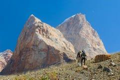 步行在塔吉克斯坦山的两个人 库存图片