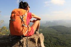 步行在山峰峭壁的妇女背包徒步旅行者 免版税库存照片