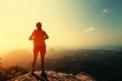 步行在山峰峭壁的妇女背包徒步旅行者 免版税图库摄影