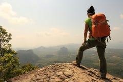 步行在山峰峭壁的妇女背包徒步旅行者 图库摄影