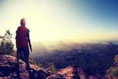 步行在山峰峭壁的妇女背包徒步旅行者 免版税库存图片