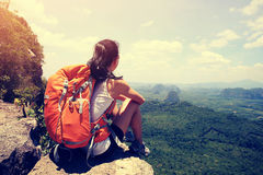 步行在山峰峭壁的妇女背包徒步旅行者 库存照片