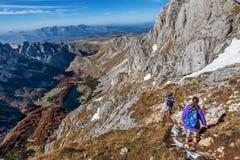 步行在山的两个小女孩在国家公园Durmit 免版税库存照片