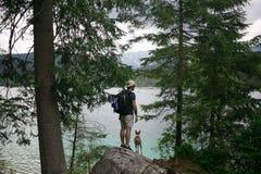 步行在有狗的高山湖的游人 免版税库存照片