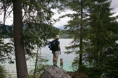 步行在有狗的高山湖的游人 免版税库存图片