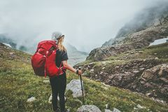 步行在有雾的山的妇女背包徒步旅行者 免版税库存照片