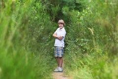 步行在森林的英俊的男孩在夏天 图库摄影