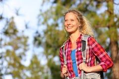 步行在森林里的年轻愉快的妇女远足者 库存图片