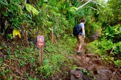 步行在沿考艾岛海岛的Na梵语海岸的著名Kalalau足迹的年轻男性游人  图库摄影