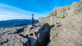 步行在海湾附近的一个人在挪威 他面对著名布道台岩石 免版税库存照片