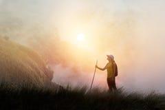 步行在薄雾的山峰峭壁的妇女背包徒步旅行者 库存图片