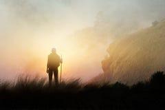 步行在薄雾的山峰峭壁的妇女背包徒步旅行者 图库摄影