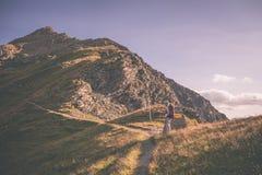 步行在被竖立路标的小径在阿尔卑斯,被定调子的图象的背包徒步旅行者 库存照片