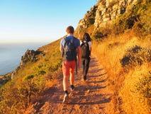 步行在途中的背包徒步旅行者对在山顶部 库存照片
