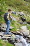 步行在阿尔卑斯的妇女,横渡一点小河 免版税图库摄影
