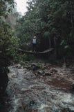 步行在雨林的一座桥梁的妇女 免版税库存照片