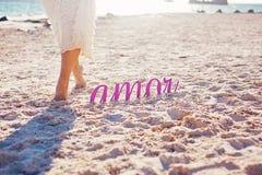 步行在黎明 女孩的腿和题字爱 库存照片