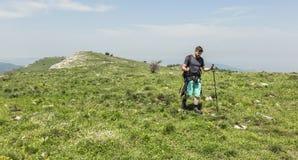 步行在绿色山的人 免版税库存照片
