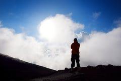 步行在Haleakala在滑的沙子的火山火山口的游人落后 下面火山口地板和云彩的美丽的景色 毛伊, 免版税图库摄影