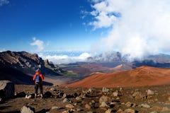 步行在Haleakala在滑的沙子的火山火山口的游人落后 库存照片