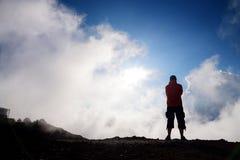 步行在Haleakala在滑的沙子的火山火山口的游人落后 库存图片