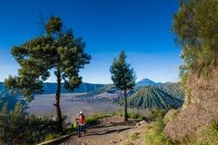 步行对在登上Penanjakan,从布罗莫火山的最佳的看法的观点的游人向下面沙子海 免版税图库摄影