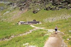 步行往在特塞尔小组,南蒂罗尔的高山小屋Oberkaseralm的妇女 库存照片