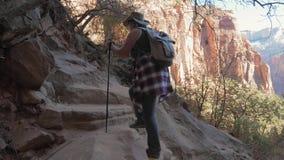 步行有困难的妇女攀登在山红色峡谷的石头步 影视素材