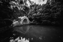 步行桥黑白照片在一个湖的在厚实的树背景中  免版税图库摄影