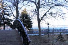步行正方形在一个公园,有一个浪漫木人行桥的 库存照片