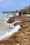 步行沿岩石海岸的妇女在波里尼西亚 库存照片