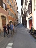 步行沿着向下一条狭窄的街道的人们在罗马观光的意大利 免版税库存照片