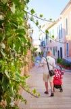 步行沿着向下一条狭窄的街道的年轻人 库存照片