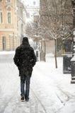 步行沿着向下下雪的城市胡同的人 免版税库存照片