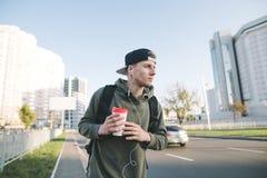 步行沿着向下他的有一杯咖啡的城市街道在他的手上和听到在Th的音乐的一个时髦的年轻人的画象 免版税图库摄影