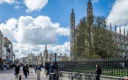 步行沿着向下剑桥街道的人们在国王` s学院,剑桥前面的一个繁忙的晴天 库存图片