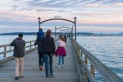 步行沿着向下历史的白色岩石码头的游人在日落 免版税库存照片