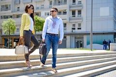 步行沿着向下台阶和微笑的企业夫妇 库存图片