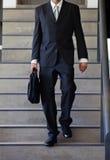 步行沿着向下台阶的商人 免版税图库摄影