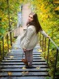 步行沿着向下台阶的女孩在一美好的秋天天 库存图片