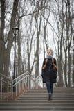 步行沿着向下台阶的美丽的红发女孩 库存图片