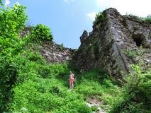 步行沿着向下在中世纪城堡的高石墙的中道路的女孩剪影在胡斯特,乌克兰 免版税库存图片