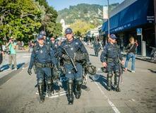 步行沿着向下在伯克利的街道的一个小组警察 免版税库存照片