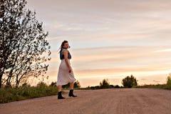 步行沿着向下在日落的路的年轻吉普赛妇女 免版税图库摄影