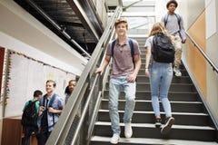 步行沿着向下在繁忙的学院大厦的台阶的高中学生 免版税库存图片