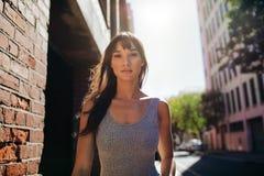 步行沿着向下城市街道的美丽的少妇 免版税库存照片