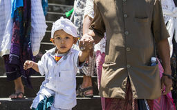 步行沿着向下寺庙台阶的巴厘语男孩握他的da的手 图库摄影