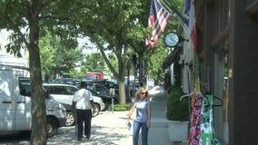 步行沿着向下有垂悬外部大厦的旗子的边路的人 影视素材