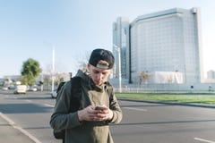 步行沿着向下有耳机的街道的一名时髦的年轻学生在他的耳朵 库存图片