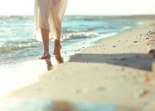步行沿着向下海滩的美丽的女孩 免版税库存图片